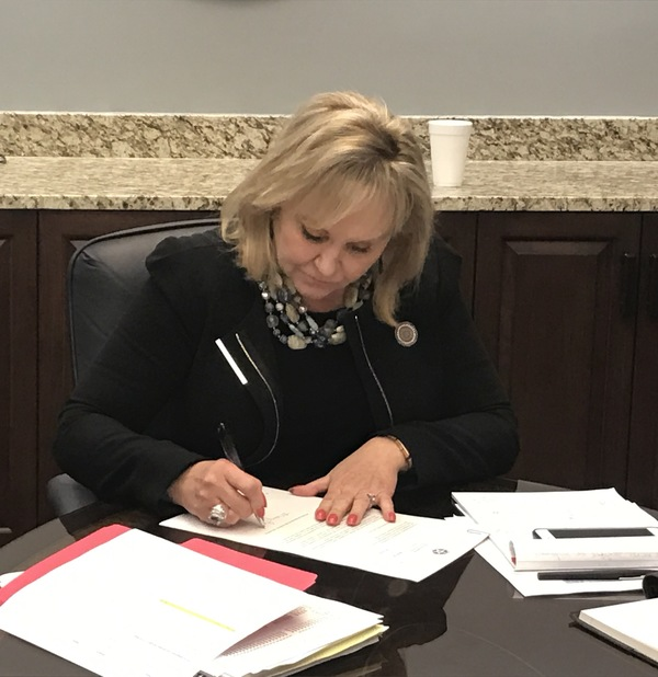 Governor Mary Fallin signs paperwork vetoing most of House Bill 1019X, a revised budget bill approved by legislators in special session. She kept intact parts of the bill that temporarily preserve funding for key health and human services until lawmakers return in another special session to approve long-term funding solutions.