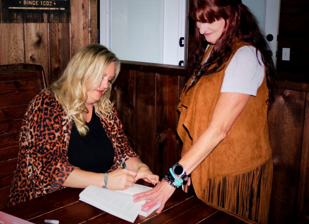Author Faith Phillips signs a copy of her newly released book, As I Lay Me Down, at an event in Okemah Friday.  (JOSH ALLEN/News Leader)