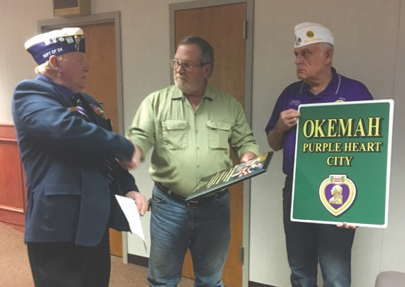 Senior Vice Commanders Mitch Reed and Ron Gott present Mayor Mike Fuller with a plaque and street signs after signing the resolution proclaiming Okemah as a Purple Heart City.
