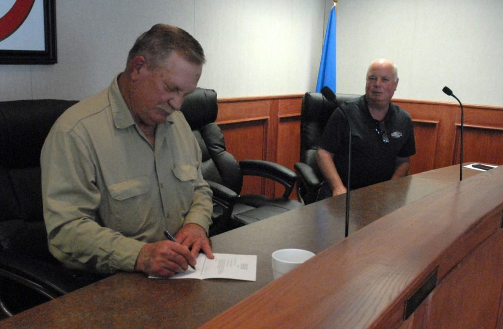 Mayor Mike Fuller signs a civil emergency proclamation fcr the City of Okemah.